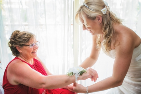 Bride puts corsage on mother before wedding