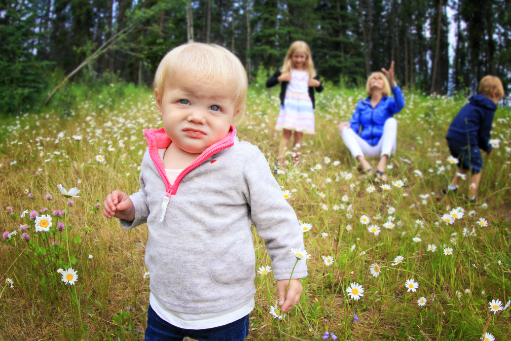 A romp in the flowers at Johnson Lake, Banff. Family Portrait Photography in Banff.