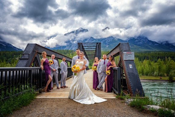 Wedding portraits of the newlyweds and their qwedding party at the Train Bridge in Canmore, AB