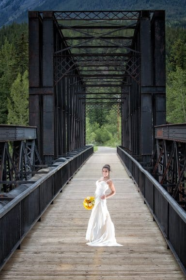 Canmore wedding photographers wedding portrait of bride at the historic Canmore train bridge in Canmore.