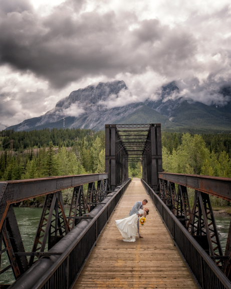 Canmore wedding photographer wedding portrait of bride and groom at the historic Canmore train bridge in Canmore.