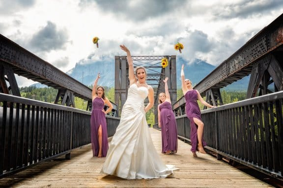 Canmore wedding photographer picture of bride with bridesmaids wedding photography at the historic Canmore train bridge in Canmore.