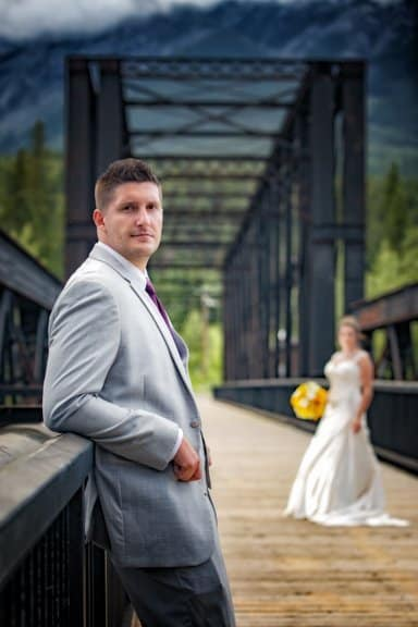 Canmore wedding photographers wedding portrait of bride and groom at the historic Canmore train bridge in Canmore.