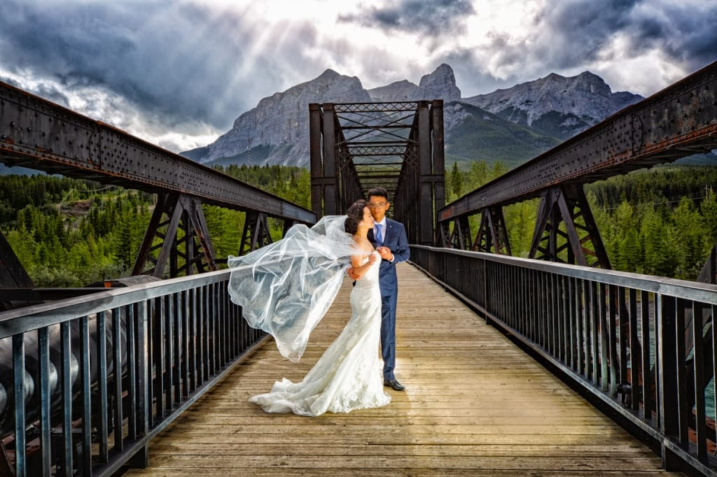 Canmore wedding photography. Wedding portrait at the Canmore train b by Canmore bridge by Canmore photographers, Burnett Photography.