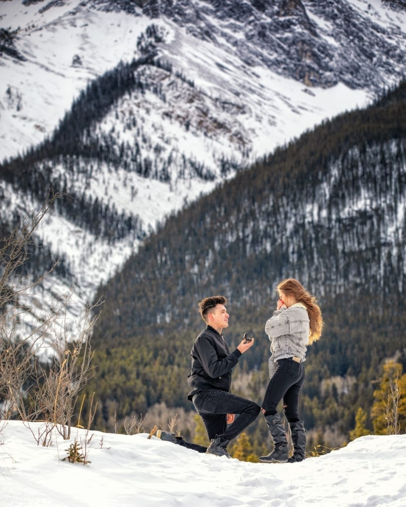 Canmore proposal photographer, Shirleen Burnett, captures newly engaged couple's portrait at the Canmore Quarry Lake with the Three Sister's in the background.