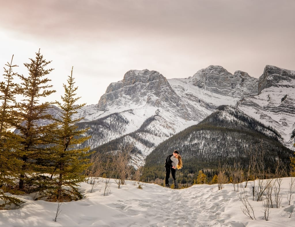 Canmore portrait photographer, Shirleen Burnett, captures newly engaged couple's portrait at the Canmore Quarry Lake with the Three Sister's in the background.
