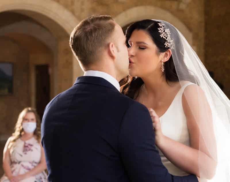 Ethical, Safe ,eco-friendly wedding Bride kissing groom at Covid wedding